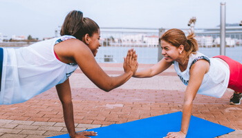 Two women doing push-ups and high-fiving each other